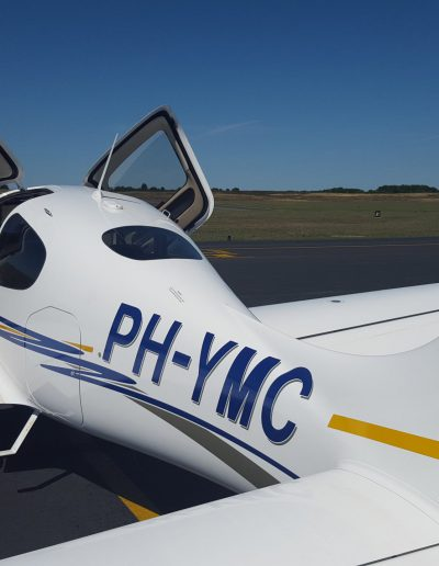 Cirrus SR20 from the side with doors open and flaps down PH-YMC